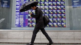 Asian-stocks - man walking in the rain in front of live rates board