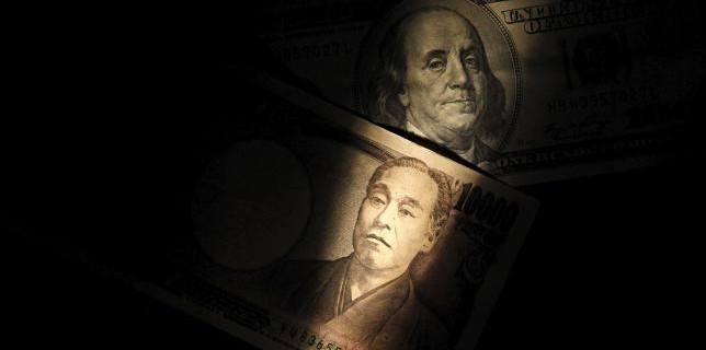 Light is cast on U.S. one-hundred dollar bill next to Japanese 10,000 yen note in Tokyo