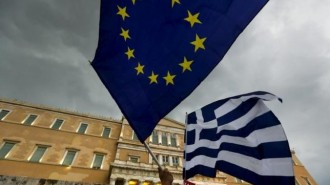Protesters wave Greek and EU flags during a pro-Euro rally in front of the parliament building, in Athens