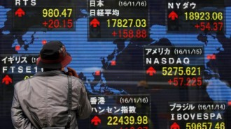 A man looks at an electronic board showing the stock market indices of various countries outside a brokerage in Tokyo