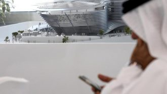 A man uses his mobile device next to a model of the Expo 2020 project in Dubai, United Arab Emirates, April 3, 2017. REUTERS/Stringer - RTX33UGT