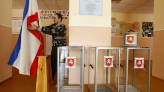 Election commission official installs Crimean flag during preparations for a referendum at the polling station in Simferopol
