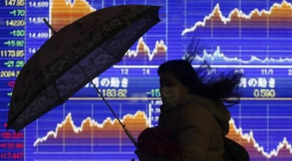 A pedestrian holding an umbrella walks past an electronic board showing the graph of the recent fluctuations of Japan's Nikkei average outside a brokerage in Tokyo February 14, 2014. REUTERS/Yuya Shino