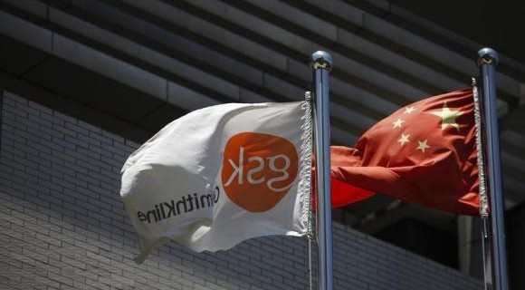 gsk flutters next to a Chinese national flag outside a GlaxoSmithKline office building in Shanghai