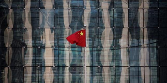 Chinese national flag flutters at the headquarters of a commercial bank on a financial street near the headquarters of the People's Bank of China, China's central bank, in central Beijing