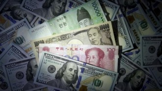 File photo illustration of South Korean won, Chinese yuan and Japanese yen notes seen on U.S. 100 dollar notes
