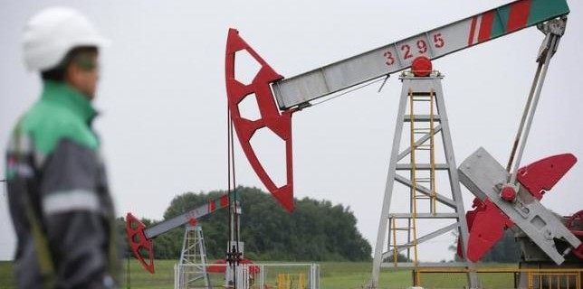 Worker looks at pump jack at oil field Buzovyazovskoye owned by Bashneft company north from Ufa