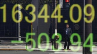 Businessman is reflected in an electronic board displaying Japan's Nikkei share average outside a brokerage in Tokyo