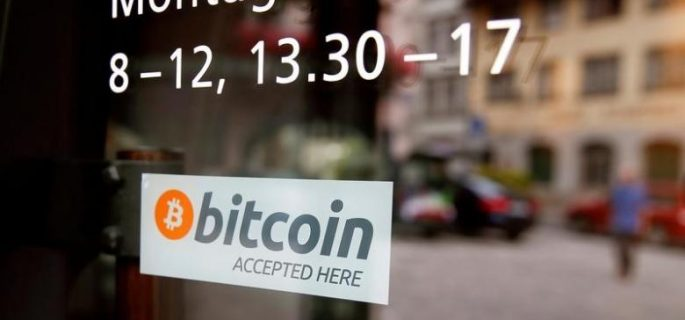 "A sticker that reads ""Bitcoin accepted here"" is displayed at the entrance of the Stadthaus town hall in Zug"