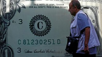 A man walks past a currency exchange bureau advertisement showing an image of the U.S. dollar in Cairo