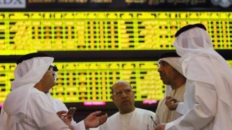 Investors speak in front of a screen displaying stock information at the Abu Dhabi Securities Exchange